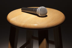 microphone-laying-wooden-stool-under-spotlight-23504944